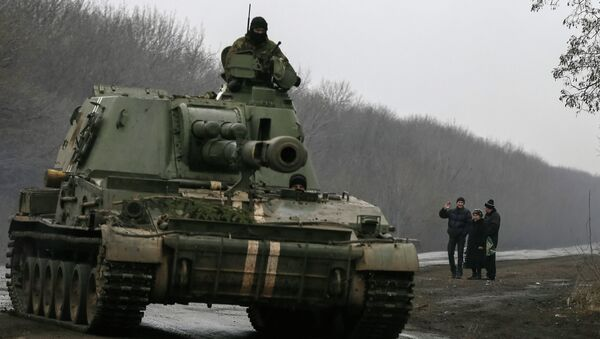 A man waves as a self-propelled howitzer of the Ukrainian armed forces drives past near Artemivsk - Sputnik Mundo