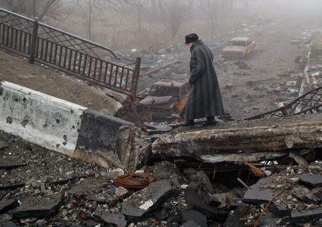 Una anciana en el puente que lleva al aeropuerto de Donetsk reducido a ruinas