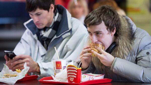 Un hombre come una hamburguesa de McDonald's - Sputnik Mundo