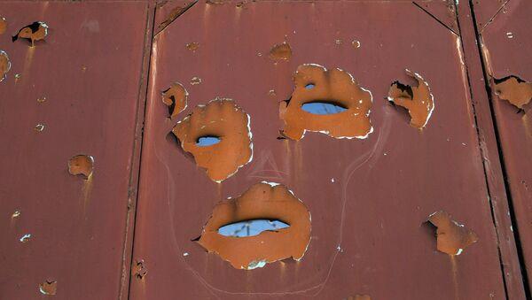 A gate filled with shrapnel holes is pictured in Donetsk's Oktyabrski district - Sputnik Mundo