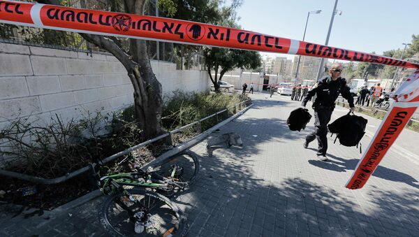 An Israeli policeman, holding bags belonging to pedestrians injured during an attack, walks past a bicycle damaged during the attack in Jerusalem March 6, 2015 - Sputnik Mundo