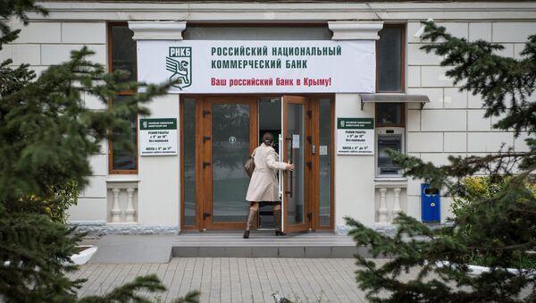 Женщина входит в здание Российского национального коммерческого банка в городе Севастополе - Sputnik Mundo