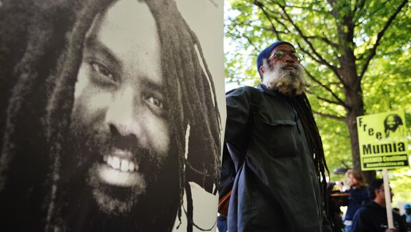 A protestor stands next to an image of Mumia Abu-Jamal outside the US Department of Justice on April 24, 2012 - Sputnik Mundo