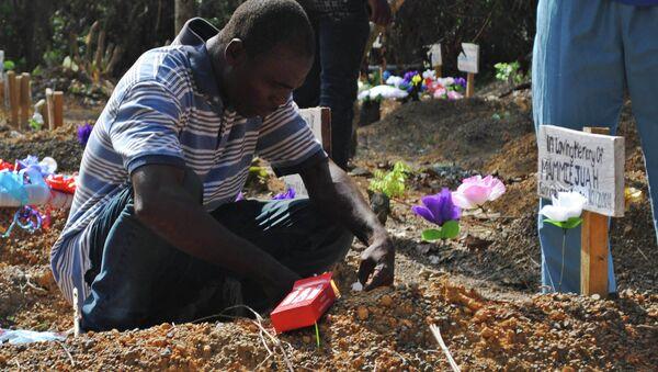 Sobreviviente del virus Ébola Stanley Juah llora en la tumba de su hijo en un cementerio para las víctimas de Ébola - Sputnik Mundo