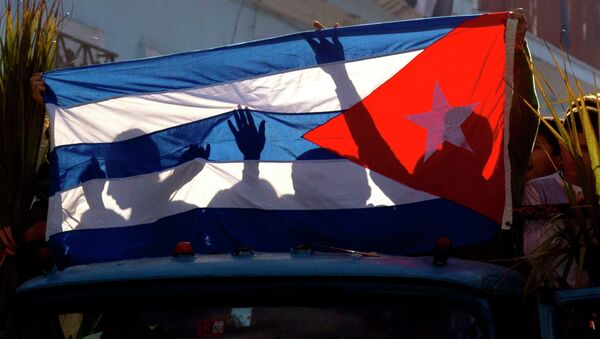 Children's shadows are cast on a Cuban national flag as they take part in a caravan tribute marking the 56th anniversary of the original street party that greeted a triumphant Castro and his rebel army, in Regla, Cuba, Thursday, Jan. 8, 2015 - Sputnik Mundo