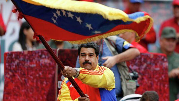Nicolas Maduro con la bandera de Venezuela - Sputnik Mundo