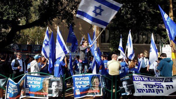 A woman waves an Israeli national flag outside a polling station in Tel Aviv March 17, 2015 - Sputnik Mundo