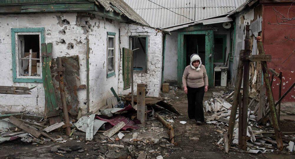 Mujer cuesta cerca de la casa destruida durante los bombardeos en Donbás