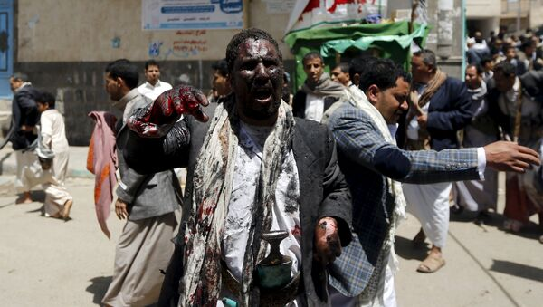 An injured man appeals for help as he waits for an ambulance outside a mosque which was attacked by a suicide bomber in Sanaa March 20, 2015. - Sputnik Mundo