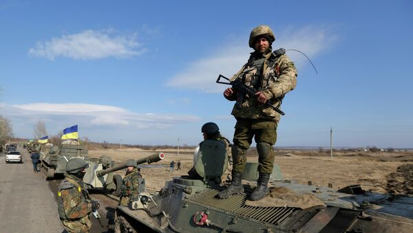 A Ukrainian serviceman stands atop an armored vehicle with canons on a road in the village of Fedorivka, eastern Ukraine, Friday, Feb. 27, 2015 - Sputnik Mundo