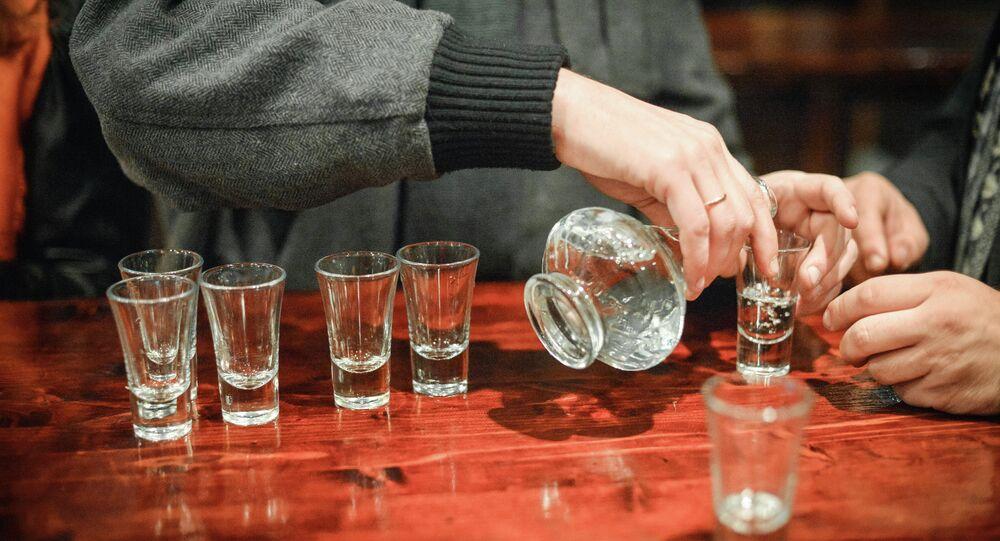 Una persona llenando vasos de alcohol