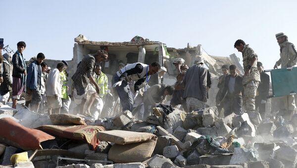 Personas desmontan las ruinas después del ataque aéreo en la capital de Yemen, Saná - Sputnik Mundo