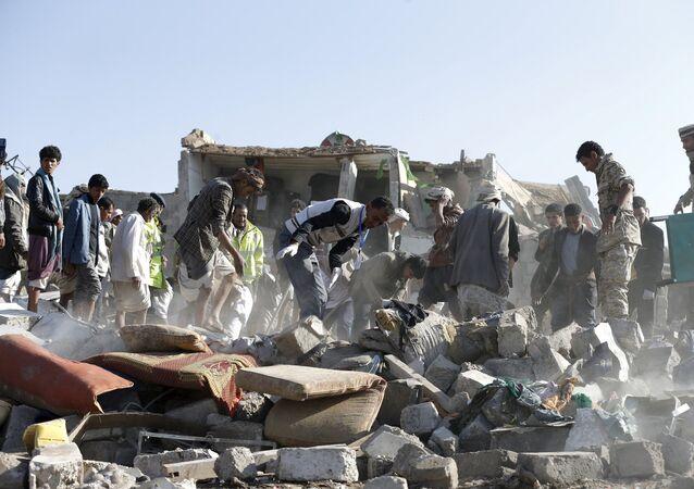 Personas desmontan las ruinas después del ataque aéreo en la capital de Yemen, Saná
