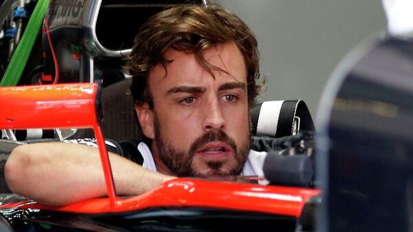 Formula One - F1 - Malaysian Grand Prix 2015 - Sepang International Circuit, Kuala Lumpur, Malaysia - 26/3/15 McLaren's Fernando Alonso sits in his car in the team garage - Sputnik Mundo