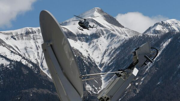 A rescue helicopter from the French Gendarmerie lands behind a media satellite dish seen during operations near the crash site of an Airbus A320, in Seyne-les-Alpes, March 26, 2015. - Sputnik Mundo