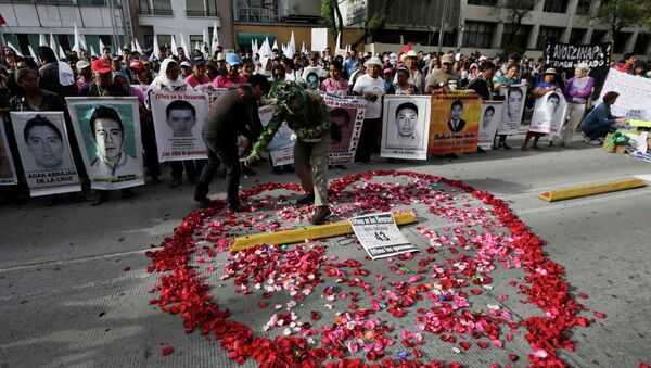 A man spreads rose petals in the shape of a heart as relatives hold up posters of some of the 43 missing students of the Ayotzinapa Teacher Training College - Sputnik Mundo