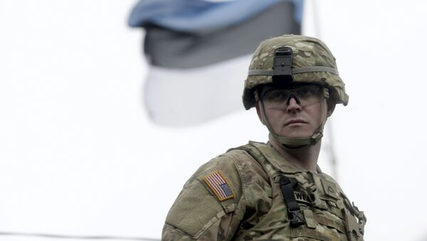 A soldier of the U.S. Army 2nd Cavalry Regiment deployed in Estonia as a part of the U.S. military's Operation Atlantic Resolve, is pictured near an Estonian flag during the Dragoon Ride exercise in Parnu March 21, 2015 - Sputnik Mundo