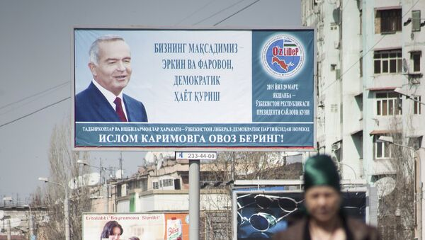 People walk in front of an election poster of Uzbekistan's President and presidential candidate Islam Karimov - Sputnik Mundo