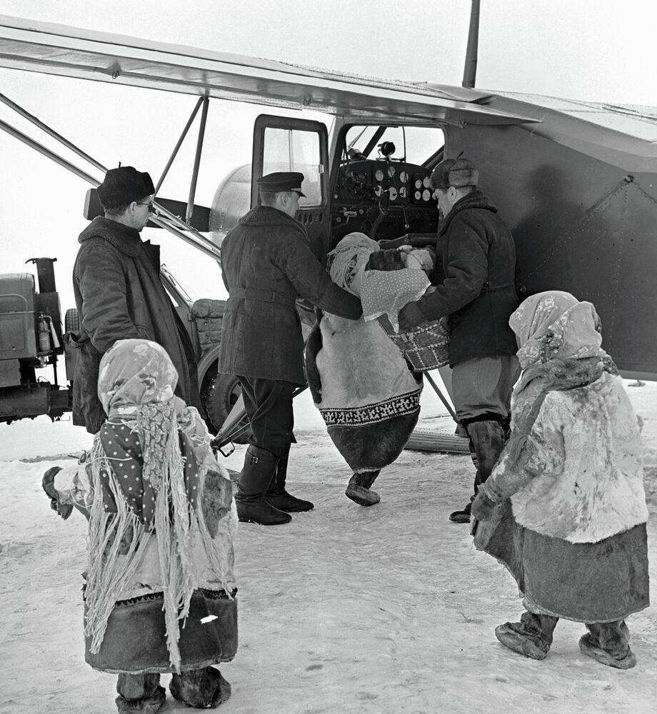 Habitantes autóctonos de Siberia suben a un avión Yak-12 en el aeropuerto de Salejard