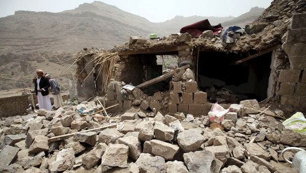 People stand on the rubble of houses destroyed by an air strike in the Okash village near Sanaa April 4, 2015. - Sputnik Mundo