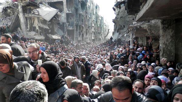Residentes del campo de refugiados palestinos Yarmuk hacen cola para recibir alimentos (archivo) - Sputnik Mundo