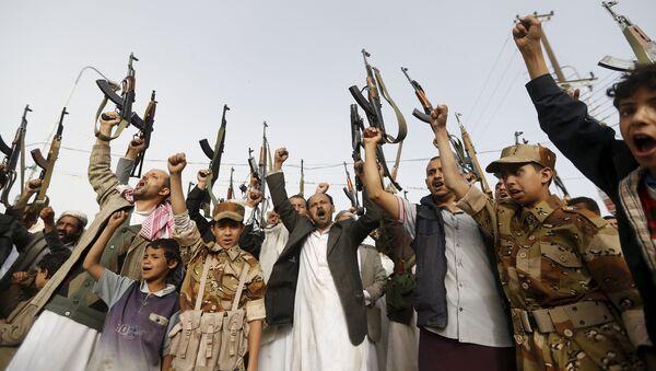 Seguidores del movimiento hutíes levantan sus rifles mientras gritan eslóganes contra los ataques aéreos saudíes en Saná - Sputnik Mundo
