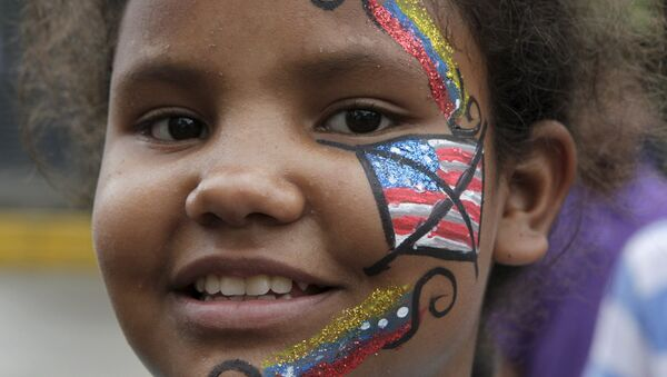 A Venezuelan girl, with her face painted with a crossed-out U.S. flag, looks on during the traditional Burning of the Judas as part of Easter celebrations in Caracas April 5, 2015. - Sputnik Mundo