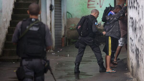 A police officer searches residents in Alemao slum complex as part of a security reinforcement by the UPP (Police Pacification Unit) in Rio de Janeiro - Sputnik Mundo