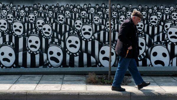 Un hombre pasa al frente de un grafiti dedicado al Holocausto (archivo) - Sputnik Mundo