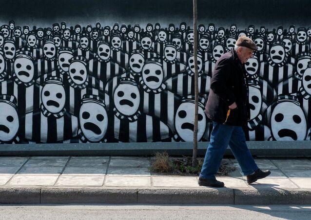 Un hombre pasa al frente de un grafiti dedicado al Holocausto (archivo)