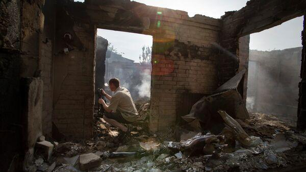 Periodista trabaja cerca de una casa destruida tras un ataque en el pueblo Semionovka, este de Ucrania - Sputnik Mundo