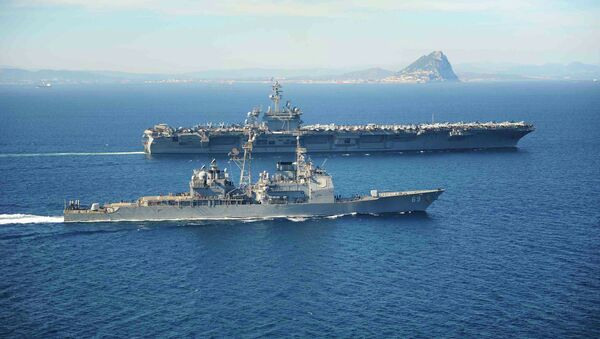The Ticonderoga-class guided missile cruiser USS Vicksburg escorts the Nimitz-class aircraft carrier USS Theodore Roosevelt (top) as they pass the Rock of Gibraltar in the Mediterranean Sea - Sputnik Mundo