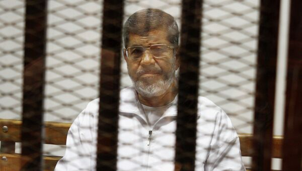 Egypt's ousted Islamist President Mohammed Morsi sits in a defendant cage in the Police Academy courthouse in Cairo, Egypt. On Tuesday April 21, 2015 - Sputnik Mundo