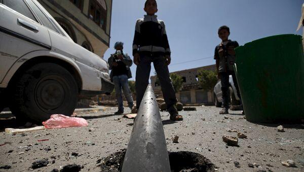 Niños miran a un proyectil  en una de las calles de Saná despues del bombardeo árabe - Sputnik Mundo