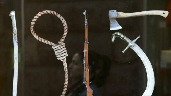 Un cartel que representa a Herramientas de Genocidio - Sputnik Mundo