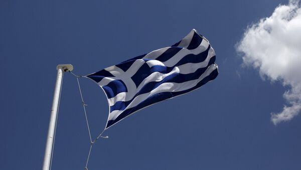 A Greek national flag flutters atop Lycabetus hill in Athens, April 22, 2015. - Sputnik Mundo