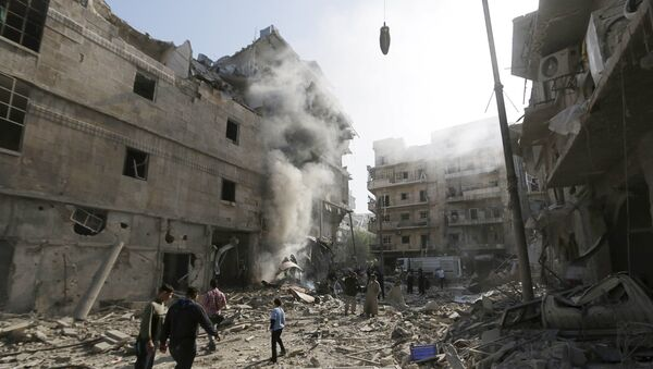 Residents walk amidst the rubble of a site damaged by what activists said was a barrel bomb dropped by forces loyal to Syria's president Bashar Al-Assad in Aleppo's al-Saliheen district - Sputnik Mundo