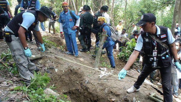 Policías cerca de una de las fosas descubiertas en Tailandia - Sputnik Mundo