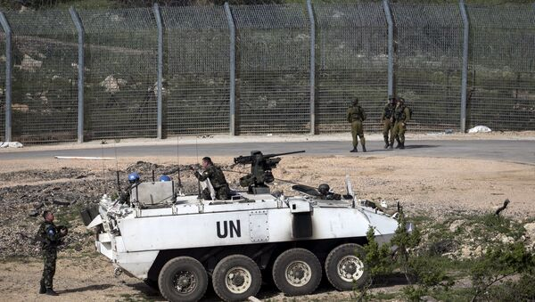 Israeli soldiers (right) and members of United Nations peacekeeping forces are seen near the frontier with Syria near Majdel Shams in the Golan Heights April 27, 2015. - Sputnik Mundo