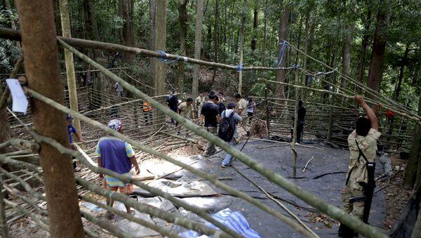 Fuerzas de seguridad y los equipos de rescate inspeccionan en el campamento abandonado en una selva en Tailandia - Sputnik Mundo
