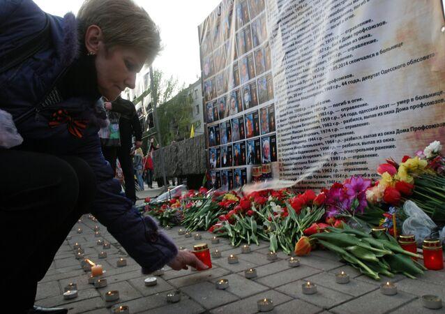 Mujer enciende una vela a los retratos de los muertos en el incendio en la Casa de Sindicatos en Odesa