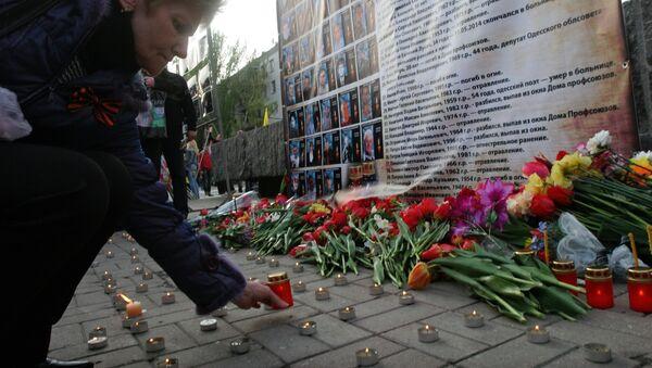 Mujer enciende una vela a los retratos de los muertos en el incendio en la Casa de Sindicatos en Odesa - Sputnik Mundo