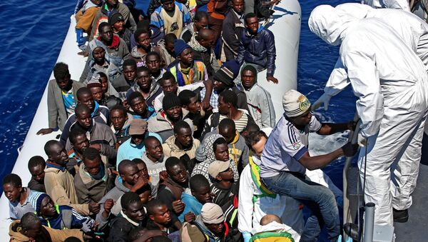 Migrants crowd and inflatable dinghy as rescue vassel  Denaro  of the Italian Coast Guard approaches them, off the Libyan coast, in the Mediterranean Sea, Wednesday, April 22, 2015 - Sputnik Mundo