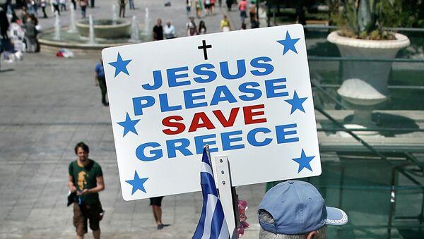Un hombre lleva una bandera griega y una pancarta que dice Jesús, salva, por favor, a Grecia - Sputnik Mundo