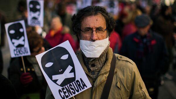 Un hombre sostiene un cartel de censura - Sputnik Mundo
