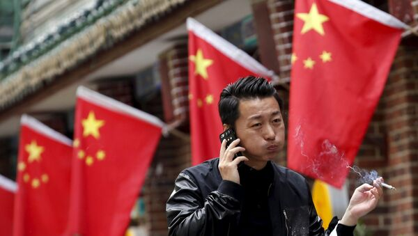 A smoker walks past Chinese national flags in front of a restaurant in Beijing, China, May 11, 2015 - Sputnik Mundo