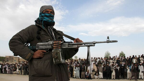 A member of the Taliban insurgent and other people stand at the site during the execution of three men in Ghazni Province on April 18, 2015. - Sputnik Mundo
