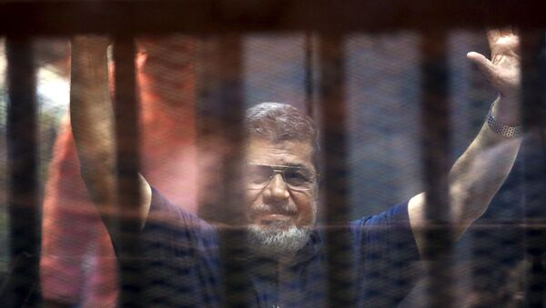 Former Egyptian President Mohamed Mursi waves as he enters for his trial with other Muslim Brotherhood members at a court in the outskirts of Cairo, May 16, 2015 - Sputnik Mundo
