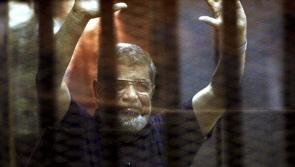 Former Egyptian President Mohamed Mursi reacts behind bars with other Muslim Brotherhood members at a court in the outskirts of Cairo, Egypt May 16, 2015. - Sputnik Mundo