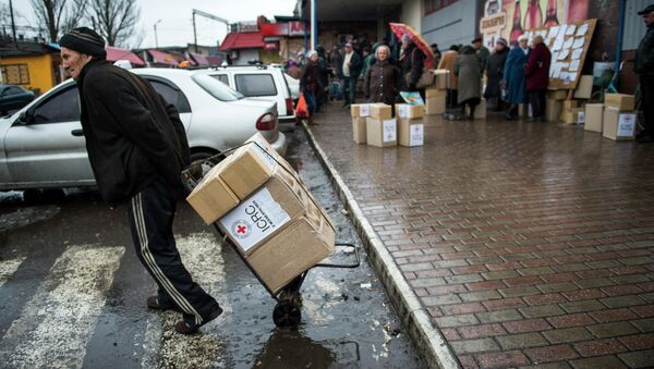A man drags a trolley with aid as he leaves a Red Cross distribution center in Debaltseve - Sputnik Mundo